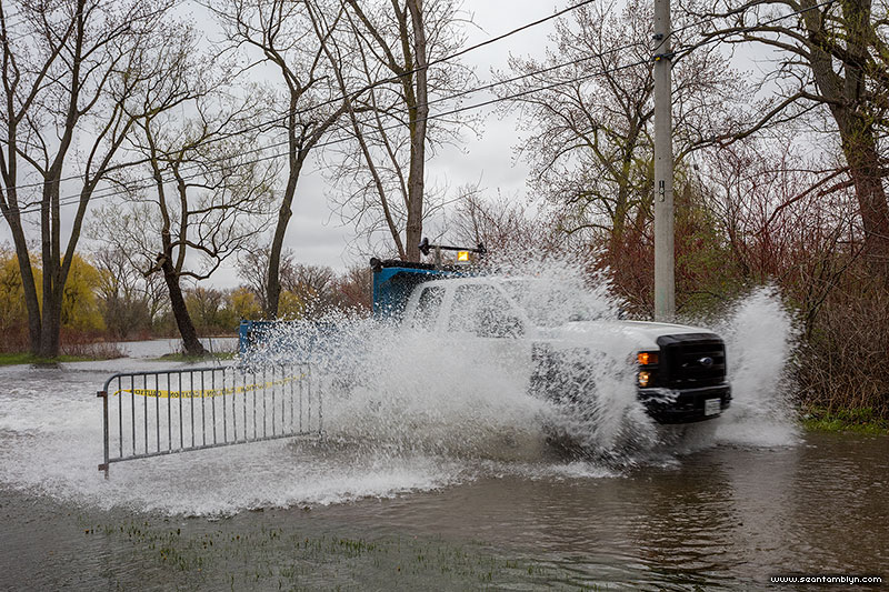 Parks vehicles run through flooded Cibola Ave, Trout Pond, Toronto Islands