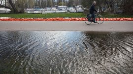 Cycling past floodwaters on Cibola Ave, Ward's Island, Toronto Islands