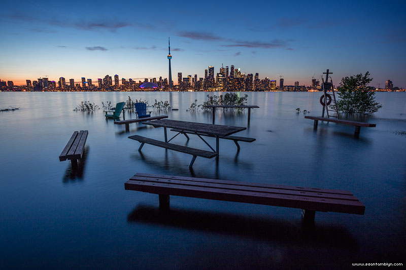 Flooded picnic area fire pit in front of Toronto skyline, Olympic Island, Toronto Islands