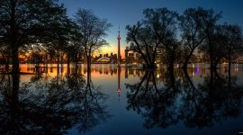 Floodwaters reflect trees and the Toronto skyline after sunset, Olympic Island, Toronto Islands